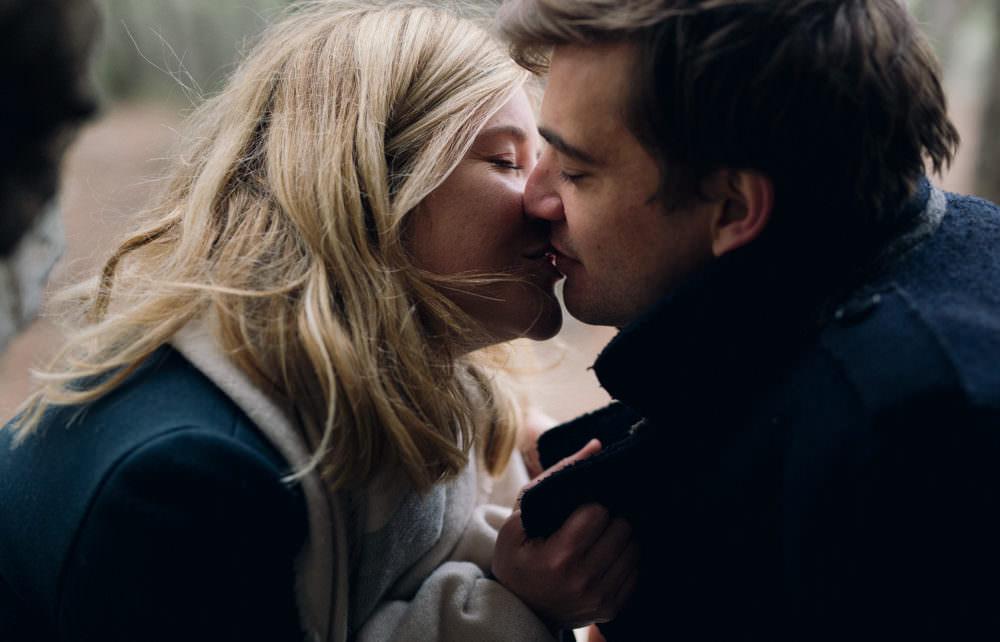 Les amoureux s'embrassent lors de leur séance engagement en forêt