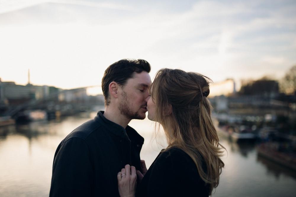 Les futurs mariés s'embrassent pendant leur séance engagement au lever du soleil à Paris