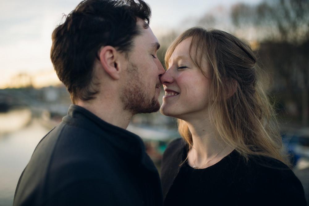 Les futurs mariés s'embrassent sur un pont parisien au lever du soleil
