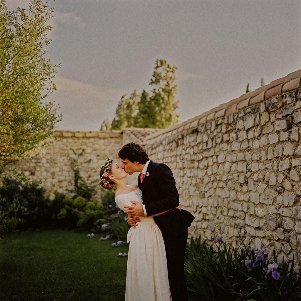 Les mariés s'embrassent dans le décor bucolique du Domaine la Bâtie
