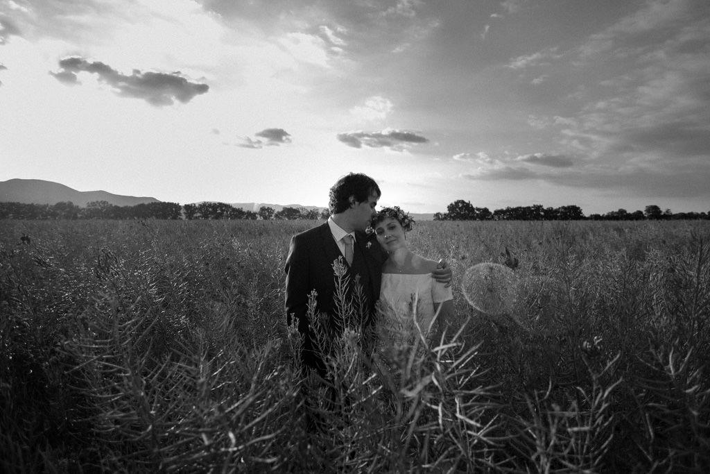 Séance couple des mariés au coucher du soleil dans un champ