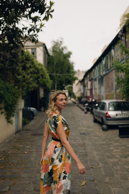 Portrait d'une femme avec une robe à fleurs de printemps dans une rue secrète de Paris
