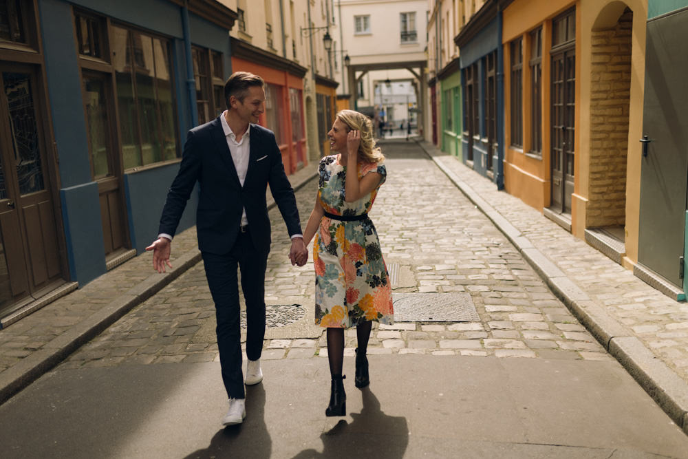 Lovers holding hands during their spring love session in a colourful Paris stree