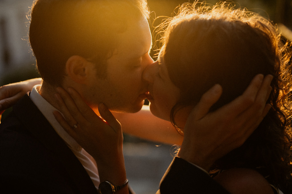 Le couple s'embrasse dans la lumière douce et dorée du lever de soleil sur Montmartre