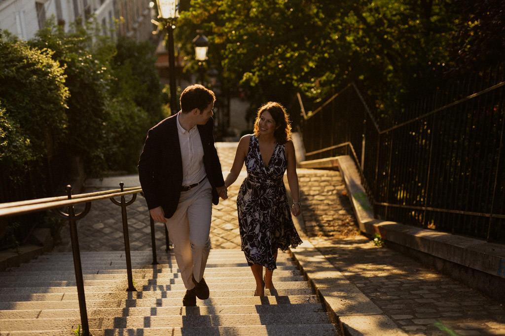 Le couple monte les marches de Montmartre dans la lumière du lever de soleil