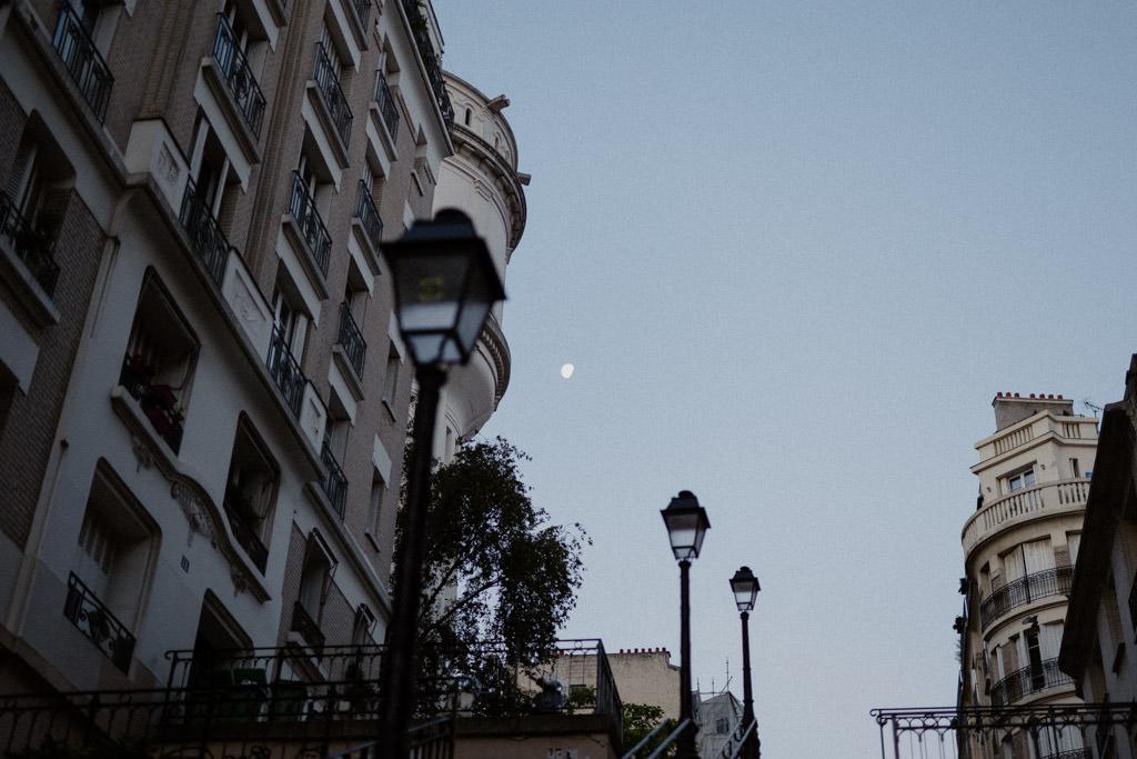 La lune brille encore juste avant le lever de soleil sur les escaliers de Montmartre