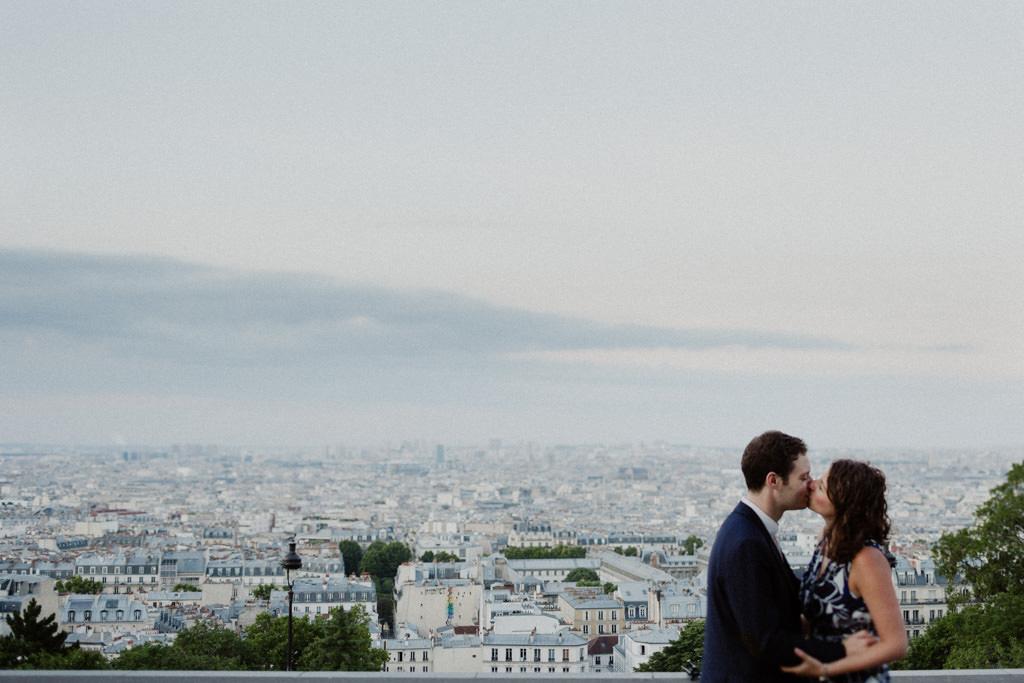 Les futurs mariés s'embrassent devant la vue de Paris depuis Montmartre à l'heure bleue - The blue hour parisian elopement kiss