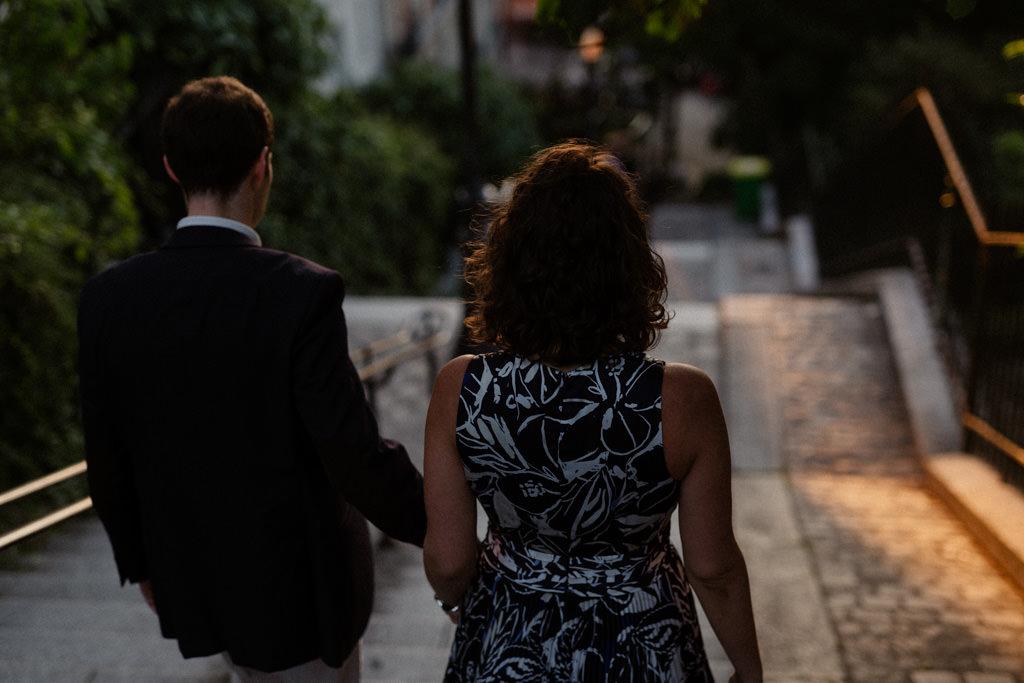 Main dans la main rejoindre la lumière du soleil levant sur les marches de Montmartre