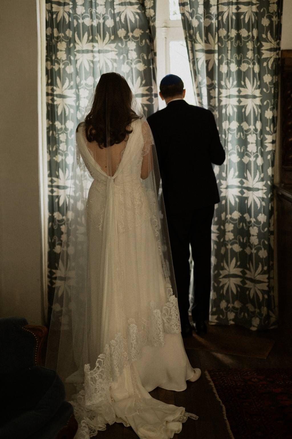 La mariée et son père attendent le rabbin pour la cérémonie en extérieur