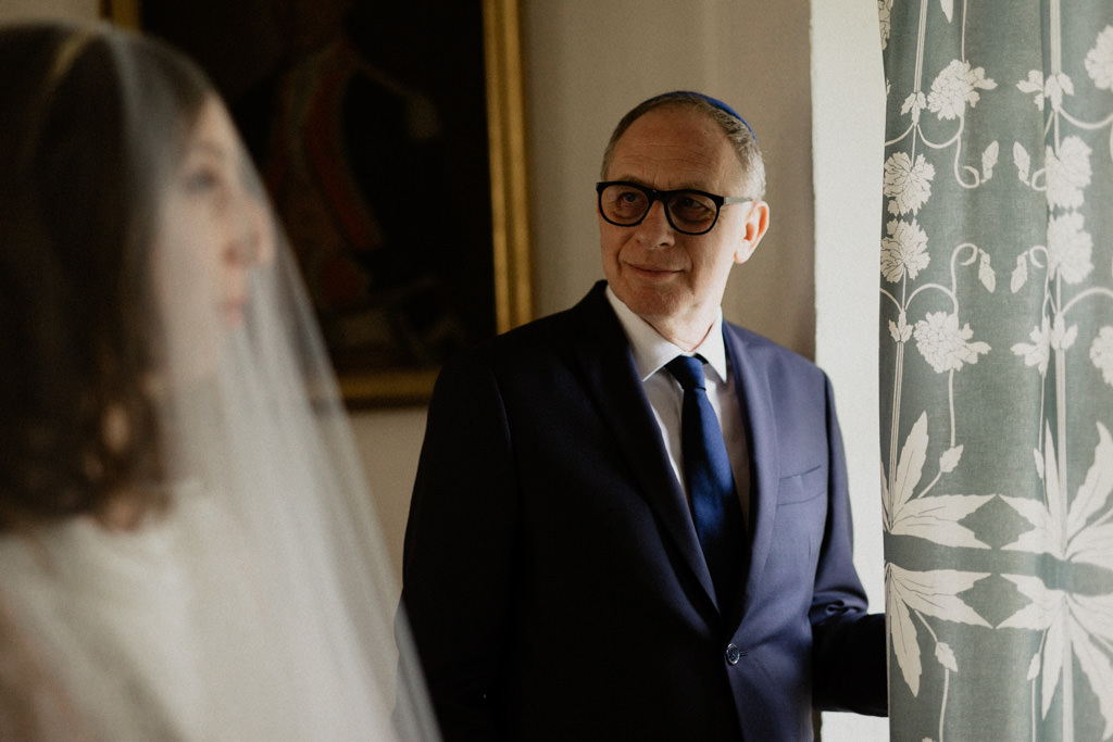 Le père de la mariée regarde sa fille avec fierté et émotion juste avant la cérémonie religieuse
