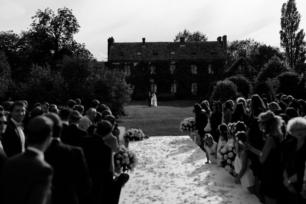 La mariée au bras de son père pour l'entrée de la cérémonie extérieure