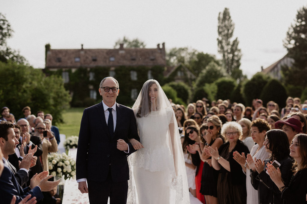 La mariée au bras de son père dans l'allée vers la houppa