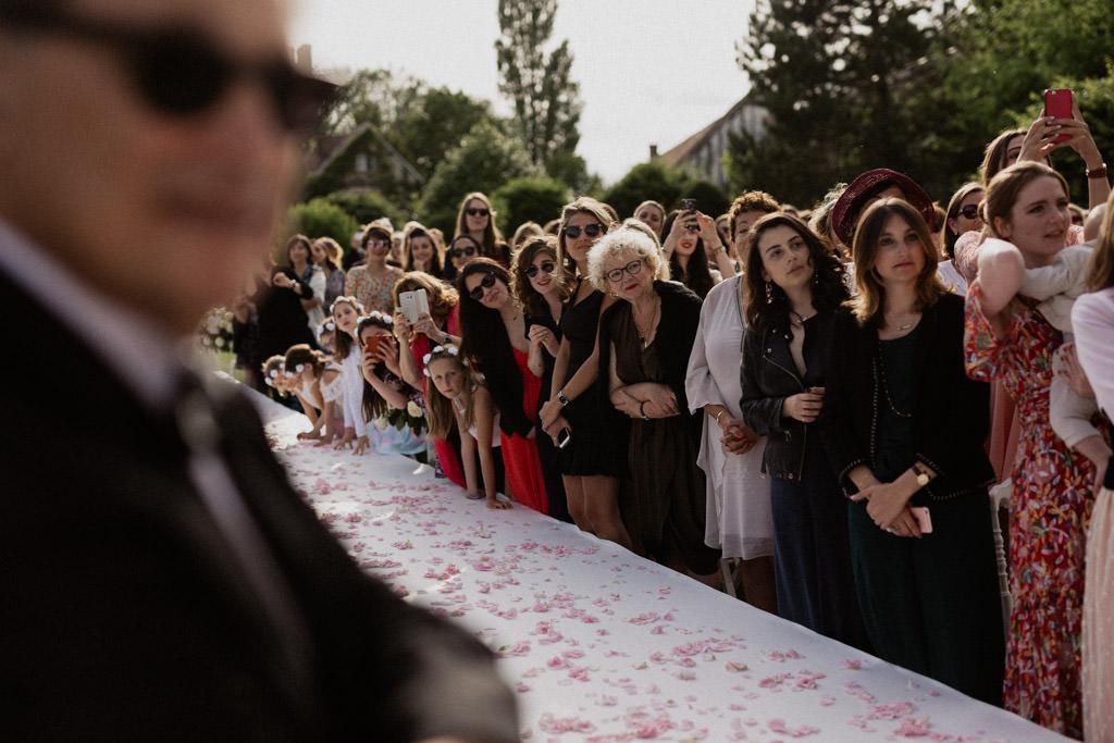 Les invités le long de l'allée se penchent pour regarder l'entrée de la mariée sous la houppa