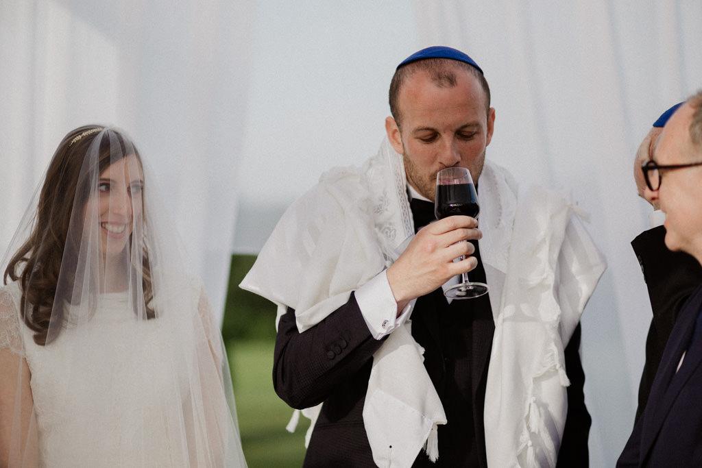 Le hatan boit le vin de cérémonie sous la houppa traditionnelle pour un mariage juif en extérieur
