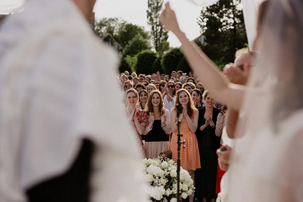 Les invités applaudissent l'échange des alliance dans le jardin du Manoir des Prévanches, Eure, France