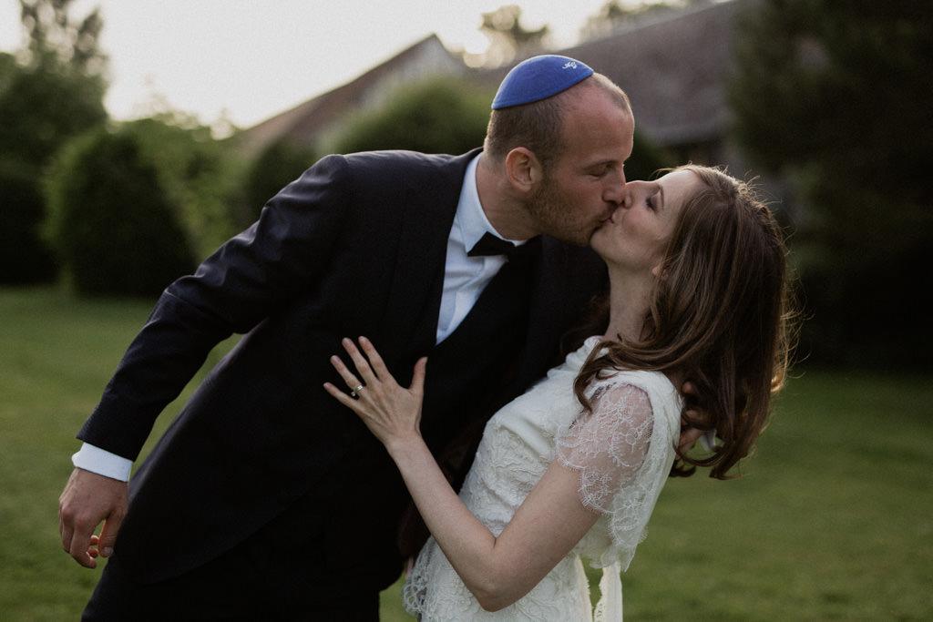 Les jeunes mariés s'embrassent dans le jardin du Manoir des Prévanches dans l'Eure