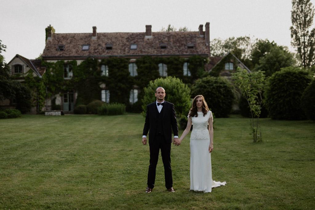 Les mariés devant la bâtisse couverte de lierre du Manoir des Prévanches