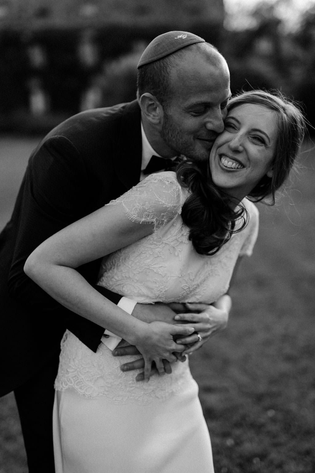 Le marié enlace la mariée pendant la séance couple dans le jardin du Manoir des Prévanches