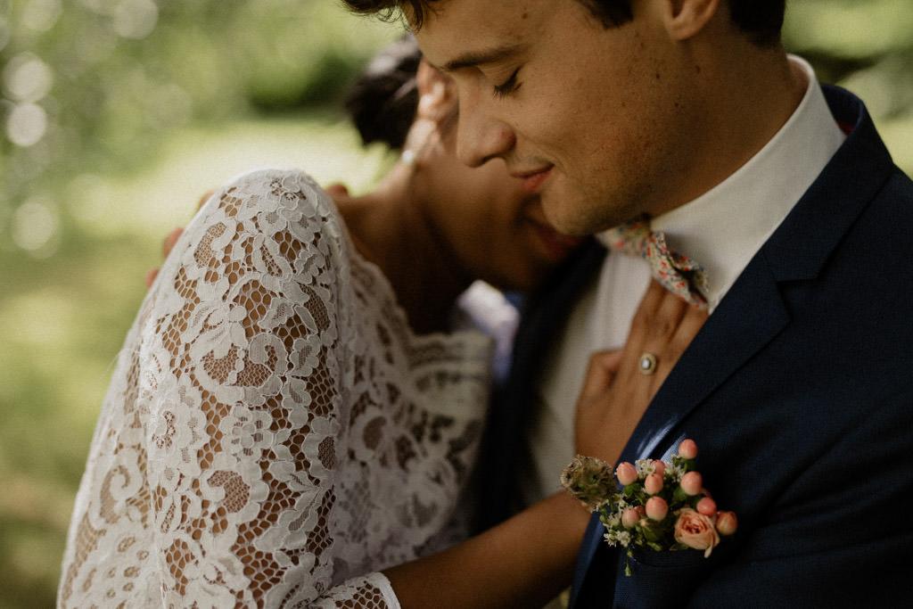 Les mariés s'enlacent sous les arbres pendant leur séance couple