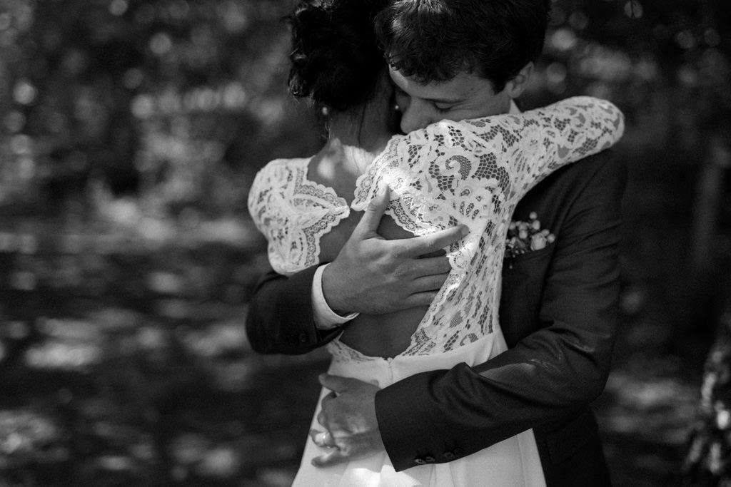 Le marié prend sa femme dans ses bras sous les arbres du jardin