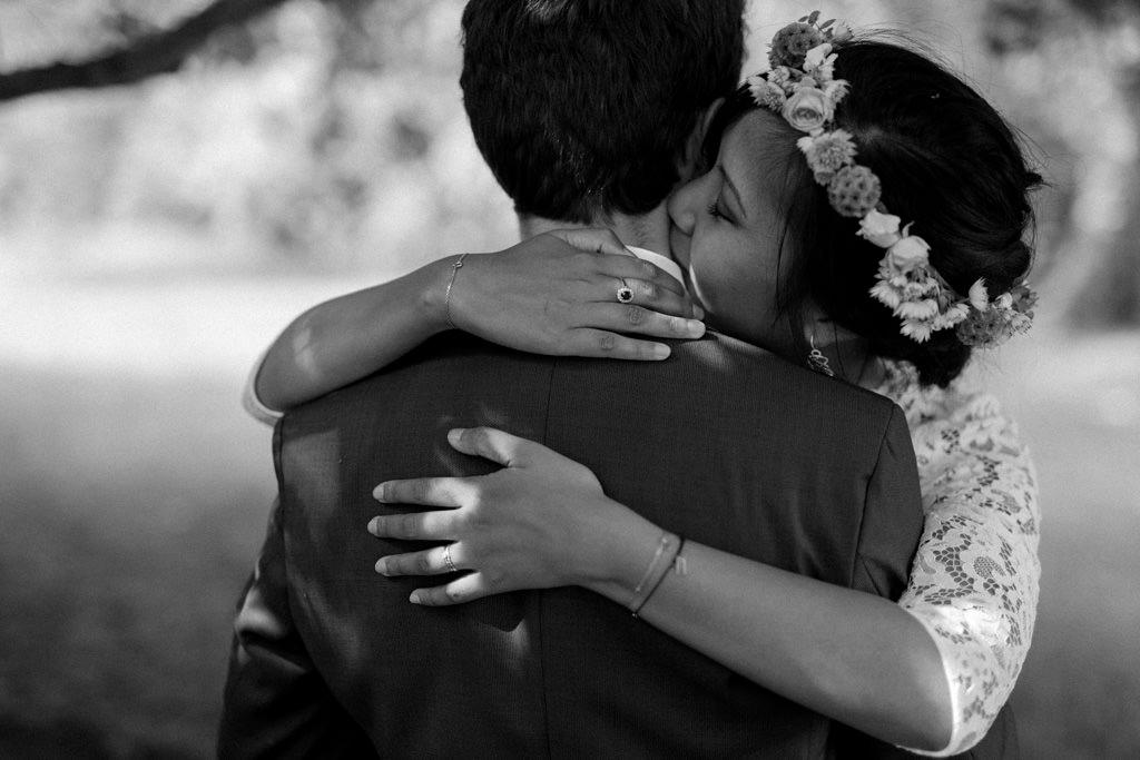 La mariée embrasse le cou de son mari sous les arbres du domaine familial