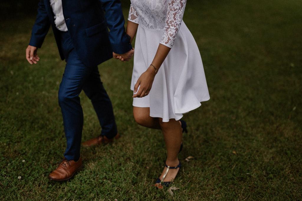 Les mariés marchent main dans la main pendant la séance couple